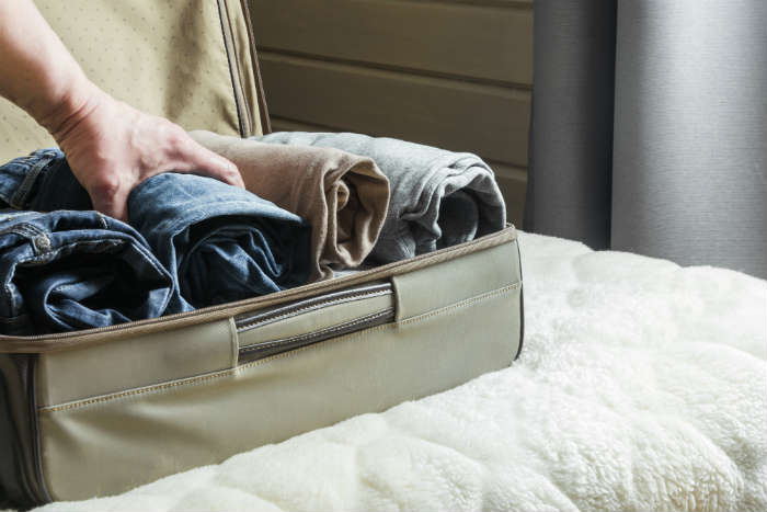 Woman Rolling Clothes In Suitcase