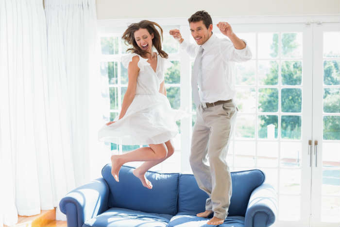 Male and female jumping on a sofa