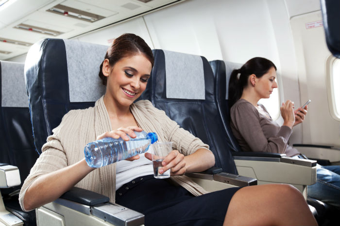 Woman Drinking Water On A Plane