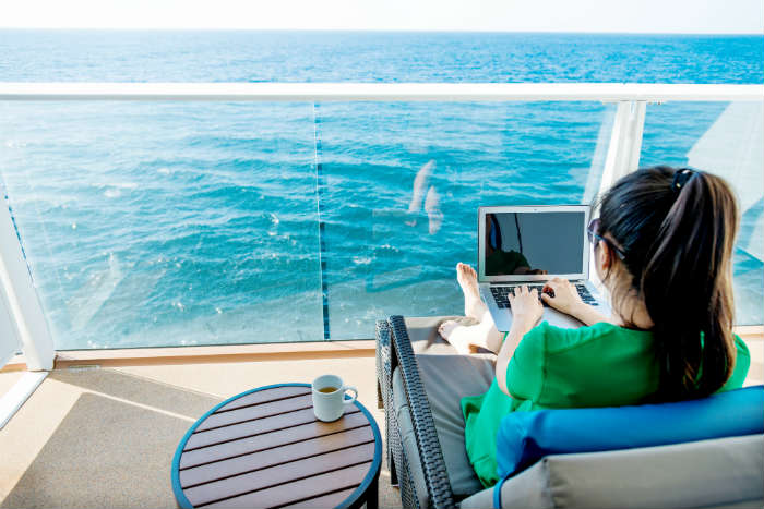 Woman using laptop on cruise cabin balcony