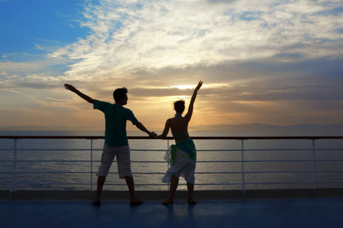 Couple with arms raised on cruise ship