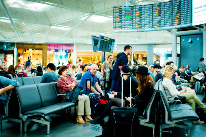 Passengers Waiting At Airport Departure Lounge