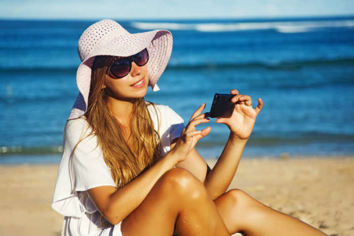 Girl on a beach with phone